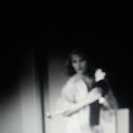 Blurred image of woman surrounded by an aura of light appears to hold a heart