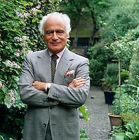 A portrait of designer John Stefanidis in the garden of his London home