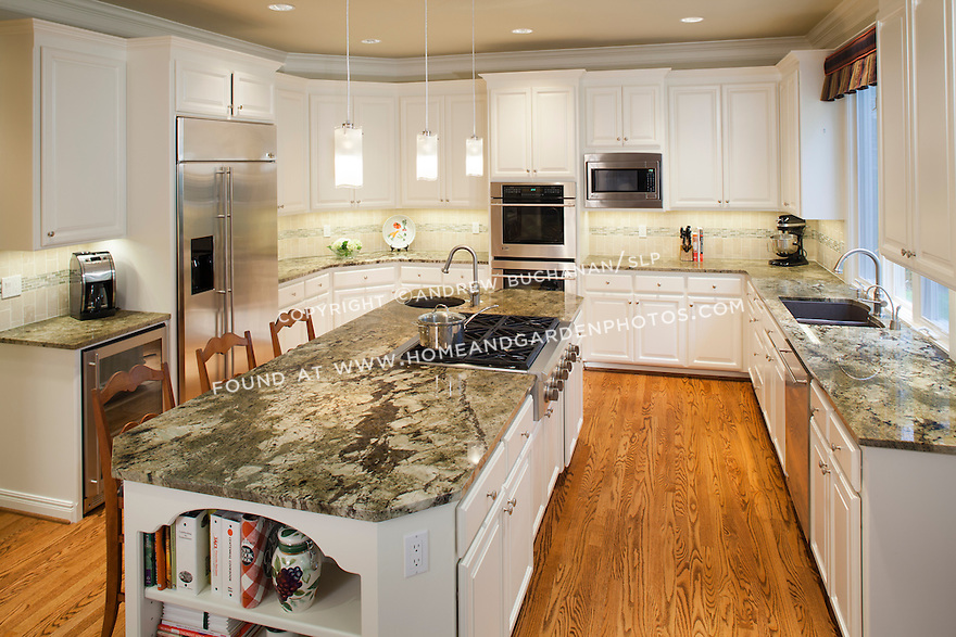 A granite-topped island is the centerpiece of a large kitchen which also features stainless steel appliances, white painted cabinetry and a neutral color palette.