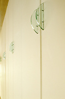A row of built-in cupboards in the lliving room has semi-circular green glass handles designed by Monic Fischer-Branunschvig