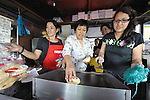 Emma Cantor (center), a regional missionary of the Women's Division of the United Methodist General Board of Global Ministries, cooking with women from a migrant ministry program in Manila that use the food sales to support their work.