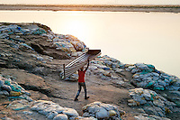 A boy carries a boat made out of aluminium to the Ganges to catch fish/ prawns near Hossaipur village. Murshidabad District, West Bengal, India.