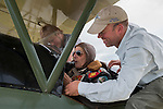 """A older passenger is strapped into the 1928 Travel Air biplane for his ride at the Aire Affaire and quipped to the guys, """"Hey, don't touch my junk!""""—cracking them up."""