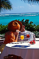 Couple kissing behind a large hat while at a cafe by the ocean