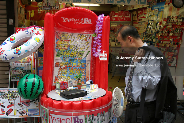 A businessman studies 'Yahoo BB' Broad Band internet service advertising in Shinjuku district of Tokyo, Japan, 27/07/04