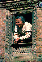 Woman at wooden carved decorated window, Patan, Nepal