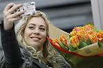 Foto: VidiPhoto<br /> <br /> ROELOFARENDSVEEN &ndash; Met champagne dopen Amy, Lisa (foto) en Shelley van OG3NE hun eigen, unieke tulp: warm oranje met gefranjerde bloemblaadjes. De zangeressen hebben de nieuwe tulp persoonlijk geselecteerd. &ldquo;We wisten meteen dat deze tulp het zou worden. De kleur staat symbool voor onze deelname aan het Eurovisie Songfestival en de gefranjerde bloemblaadjes zijn uniek en bijzonder. We zijn ontzettend trots op onze eigen tulp!,&rdquo; aldus OG3NE. De nieuwe tulp wordt aangeboden door de Nederlandse tulpenkwekers. De doop vond plaats bij tulpenkwekerij Wesselman Flowers in Roelofarendsveen. Tulpenpromotie Nederland (TPN) zorgt dat de naam van de nieuwe tulp wordt vereeuwigd in het International Cultivar Register of Tulip Names. Het veredelingsproces van deze tulp duurde 19 jaar. De OG3NE-tulp is vanaf volgend jaar mondjesmaat verkrijgbaar zal zijn. OG3NE bestaat uit de zussen Lisa, Amy en Shelley. De bandnaam is een samentrekking van O (de bloedgroep van hun moeder) en G3ne (de genen die hen met elkaar verbinden). Dit jaar vertegenwoordigt OG3NE Nederland op het Eurovisie Songfestival in Kiev. Hun muzikale inzending zal in maart bekend worden gemaakt.