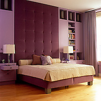 In the bedroom of a New York apartment the stunning floor-to-ceiling headboard of the double bed is upholstered in a rich violet velvet