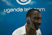 """Demonstrating the 'Kasana' or Sun, a solar powered phone - """"No Power No Worries"""" read the adverts. Available from Uganda Telecom,they've had equiries from Rwandans who want to use their phone. RTE, the Chinese manufacturer claims that 18 hours of bright sun will provide a full recharge."""