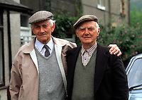 Portriat of two senior Welsh men who are old friends, in a casual embrace. Wales.