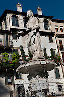 """Low angle view of the fountain of Madonna Verona, 4th century, Piazza delle Erbe, Verona, Italy. The Piazza delle Erbe (Square of Herbs) stands on the old Roman Forum, and remains the centre of city life. In the centre of the square is a fountain built in 1368, perhaps by Bonino da Campione with a 4th century Roman statue, known as the """"Madonna Verona"""". Picture by Manuel Cohen."""