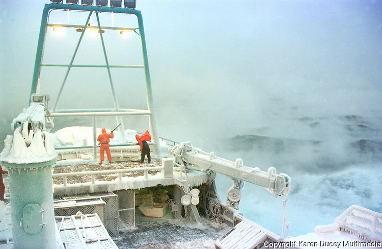 "Ice fog surrounds the Crab fishing vessel Kiska Sea is as it fishes for opilio crab in the Bering Sea in January and February of 1995. Also known as freezing spray, waves and wet sea air slam into the boat freezing on impact causing ice to cover the boat. Newton is carrying a sledgehammer which he is using to beat the ice off the sides of the boat. Boats covered in ice become top heavy and are in danger of rolling over. The Bering Sea is known for having the worst storms in the world. Crab fishing in the Bering Sea is considered to be one of the most dangerous jobs in the world. This fishery is managed by the Alaska Department of Fish and Game and is a sustainable fishery. The Discovery Channel produced a TV series called ""The Deadliest Catch"" which popularized this fishery."
