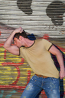 man kissing his bicep while standing in front of a graffiti metal gate in New York City