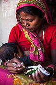 28 year old Asha Devi breastfeeds her 11 month daughter, Sharda in her house in Saptari, Nepal. <br /> Asha Devi got married when she was 14. She got pregnant after 6 months of her marriage. Her first child survived for 6 days, she woke up next to a dead baby. She was pregnant two months later. Asha Devi's 2nd daughter survived for 9 months and later died due to prolonged fever. 3 months after her daughter died, Asha was pregnant again and within w months, she had spontaneous abortion. She was pregnant with Radha Kumari mandal who was acutely malnourished. Radha was admitted when she was 36 months old on October, 20th 2013. MUAC - 110 mm, Weight - 7 kg, Height - 75 cm. Radha was discharged on Dec 6, 2013 - her MUAC at the time of discharge was 128mm, Weight 8.8kg and height- 75.5 cm. She consumed 100 sachets of RUTF and gained 5gm/day while on the programme. <br /> Rukmini, her second daughter was born a year after Radha was born. Rukmini was severely malnourished too. She was admitted on Feb 16th, 2014. Her MUAC was 119mm, weight - 11 kg, and height - 96 cm. Her third daughter Sharda is severely malnourished. Sharda is under RUTF.  <br /> Asha Devi is pregnant for the 7th time and is 6 months pregnant.