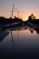 Reflection of telephone poles and wires  in a flooded street in Southampton, NY