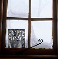 A metal mongrammed stencil propped against a window seems to epitomise the harsh winter weather outside
