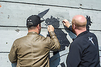 Street art enthusiasts inspect and clean damage done by a vandal to the seventeenth installment of Banksy's graffiti art in the Williamsburg neighborhood of Brooklyn in New York on Thursday, October 17, 2013.  The elusive street artist is creating works around the city each day during the month of October. (© Frances M. Roberts)