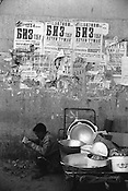 A stall holder in Chorsu Bazaar, selling metal pots and pans, reads the newspaper,  Bishkek,  Kyrgyzstan.