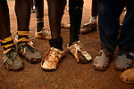 Young men playing football in old broken boots and plastic sandals train next to the national stadium. Yaounde, Cameroon.