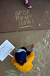 A child draws on the sidewalk at the CROP Hunger Walk, held October 27, 2013, in Raleigh, North Carolina.