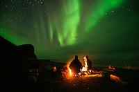 sitting around an campfire with northern lights - aurora borealis in the sky overhead, Unstad, Vestvågøy, Lofoten Islands, Norwya