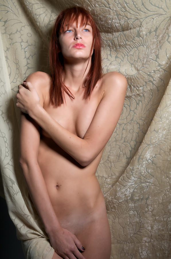 Sensual red-hair model nude with silk backdrop.