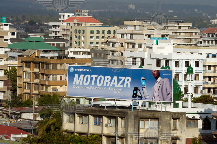 Rooftop billboard avertising Motorola mobile telephones, surrounded by apartment blocks and modern high-rise buildings...