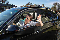 Young female commuter screaming out car window with arms raised in anger at the never ending Austin traffic nightmare in Austin, Texas.