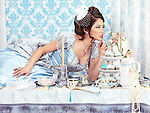 Beautiful woman in a fancy blue dress lying on a tea party table