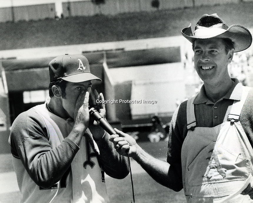 """Farmers Day at the Oakland Alameda County Coliseum Jim """"Catfish"""" Hunter does a """"hog call"""" for Monte Moore. (photo/Ron Riesterer)"""