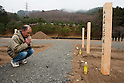Onagawa, Japan - A photo made available on April 11 shows Yoshikatsu Hiratsuka, 66, pray where his wife and mother rest in peace at a temporary mass grave for the March 11 earthquake and tsunami victims. Yoshikatsu was visiting a friend at the time the earthquake hit and he quickly rushed back home to later see his wife and mother in front of the house thinking how to escape. Before the two could react to a plan to escape, the 10-meter tsunami swept them away, leaving Yoshikatsu to live. His son is still missing and continues to search for him everyday. (Photo by Christopher Jue/AFLO) [2331] **ITALY OUT**