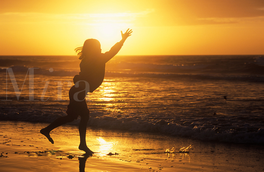 Atlantic Ocean Sunrise with young girl raising her hands to the sun.