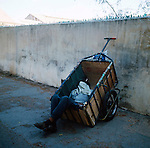 Man with a cart sleeping in his cart with a cloth over his face.Cassablanca,Morocco. 1975