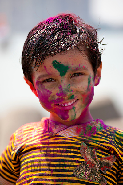 Indian boy celebrating Hindu Holi festival of colours with powder paints in Mumbai, India