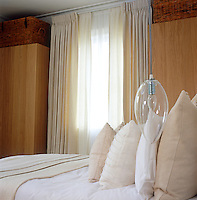 The palest of oyster pinks, cream and white have all been used in the bedding and curtains of this bedroom