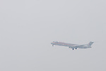 Under heavy fog conditions, an American Airlines jet plane approaches Chicago's O'Hare International Airport for a landing.