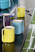 A set of brightly coloured ceramic mugs on the black kitchen work surface