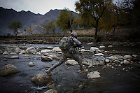 A soldier from 3rd Platoon, Charlie Company, 1-26 Infantry crosses a river as he returns to base following a meeting with village elders.