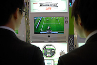 Game show visitors play Konami's Winning Eleven 2009 software for the Xbox360.