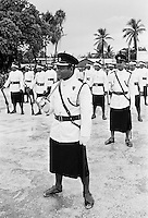 Soldiers in traditional uniforms wearing skirts in military parade in Kiribati, South Pacific