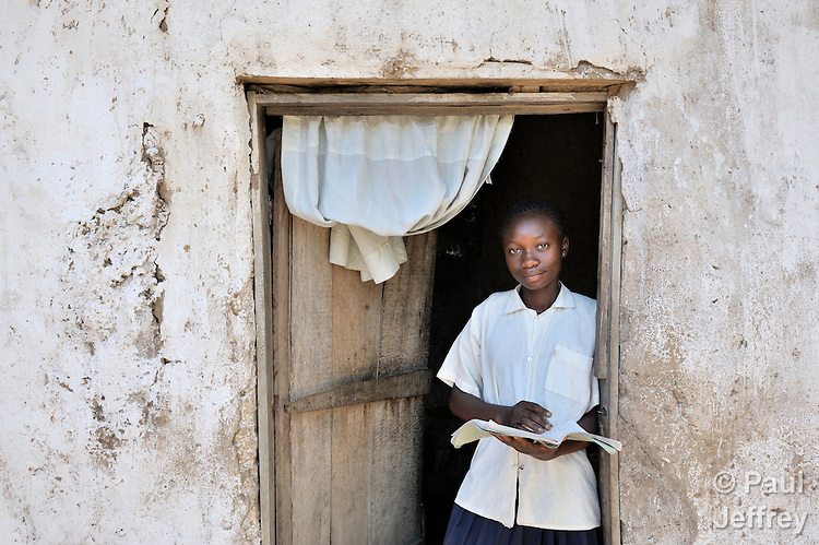 Numbi Kalamba, 13, does her homework in the door of her one-room home in the Katuba neighborhood of Lubumbashi, in the Democratic Republic of the Congo. She receives school supplies, mentoring, a uniform, and a scholarship for school fees from the United Methodist Committee on Relief (UMCOR).