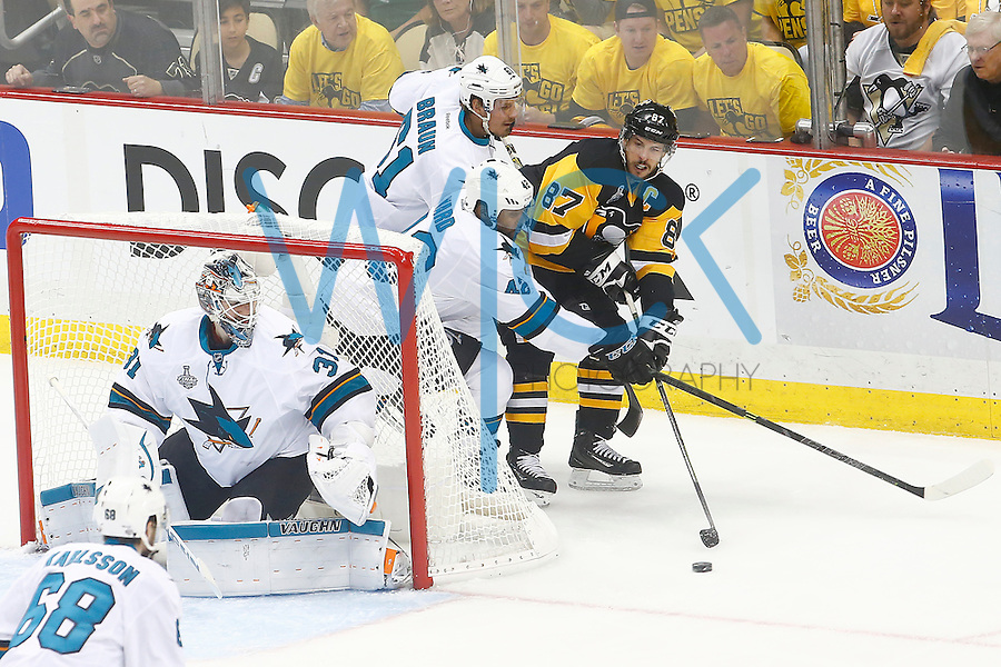 Sidney Crosby #87 of the Pittsburgh Penguins passes the puck behind the net in front of Martin Jones #31 of the San Jose Sharks in the first period during game one of the Stanley Cup Final at Consol Energy Center in Pittsburgh, Pennslyvania on May 30, 2016. (Photo by Jared Wickerham / DKPS)