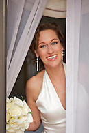 Portrait of bride holding bouquet looking out window.