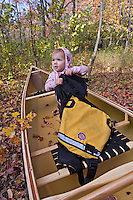 A young girl plays in a green canoe on a fall day near Marquette Michigan.