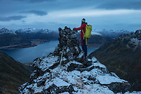 Female hiker stands next to summit cairn on Persatind, Gimsøy, Lofoten Islands, Norway