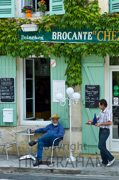 Waiter serves customer Pastis at traditional French Cafe in town of Castelmoron d'Albret in Bordeaux region, Gironde, France