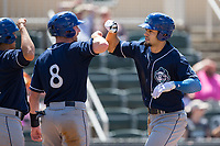 Willie Abreu (right) of the Asheville Tourists bumps forearms with teammate Vince Fernandez (8) after hitting a home run against the Kannapolis Intimidators at Kannapolis Intimidators Stadium on May 7, 2017 in Kannapolis, North Carolina.  The Tourists defeated the Intimidators 4-1.  (Brian Westerholt/Four Seam Images)