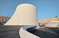 Le Volcan or the Volcano, auditorium opened 1982, designed by Oscar Niemeyer, 1907-2012, and Jean-Maur Lyonnet, at the Maison de la Culture du Havre, Le Havre, Normandy, France. Behind are apartment buildings designed by Auguste Perret, 1874-1954, who led the reconstruction of Le Havre in the 1950s, after the town was completely destroyed in WWII. The large volcano contains a 1200 seat theatre and 350 seat cinema, while the small volcano (right) has a 500 seat hall and 80 seat auditorium and is now used as a reference library. The forum is built from concrete and the buildings are linked and accessed via ramps. The centre of Le Havre is listed as a UNESCO World Heritage Site. Picture by Manuel Cohen