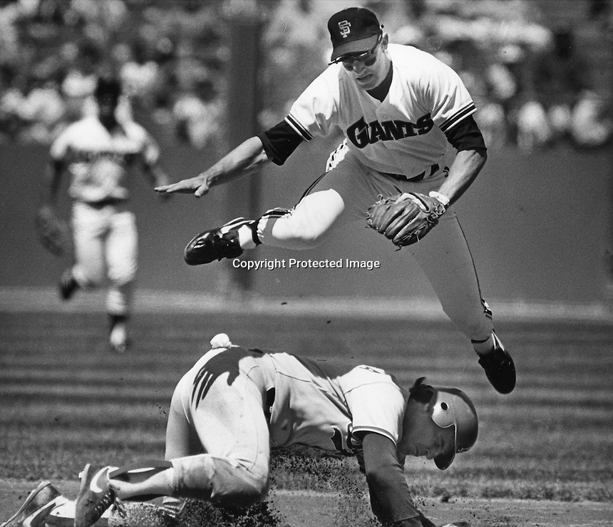 San Francisco Giants Robby Thompson jumps over Los Angles Dodger Mike Scioscia to complete doubleplay.<br />