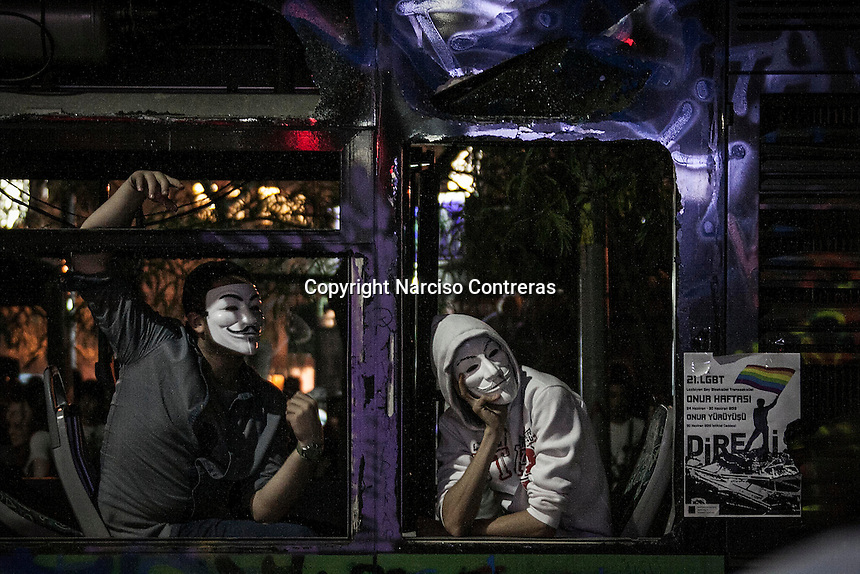 In this Friday, Jun. 07, 2013 photo, Protesters covered with masks sit inside a burned bus during a 24/7 masive rally against the turkish government in Istanbul, Turkey. (Photo/Narciso Contreras).